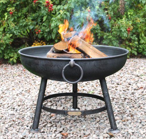 Classic fire pit lit in garden